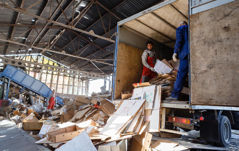Выгрузка макулатуры из грузовика на производственно-заготовительном предприятии